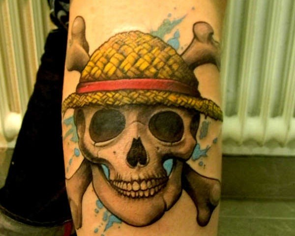 Pirate smiling skull in funny hat and crossed bones colored tattoo on forearm