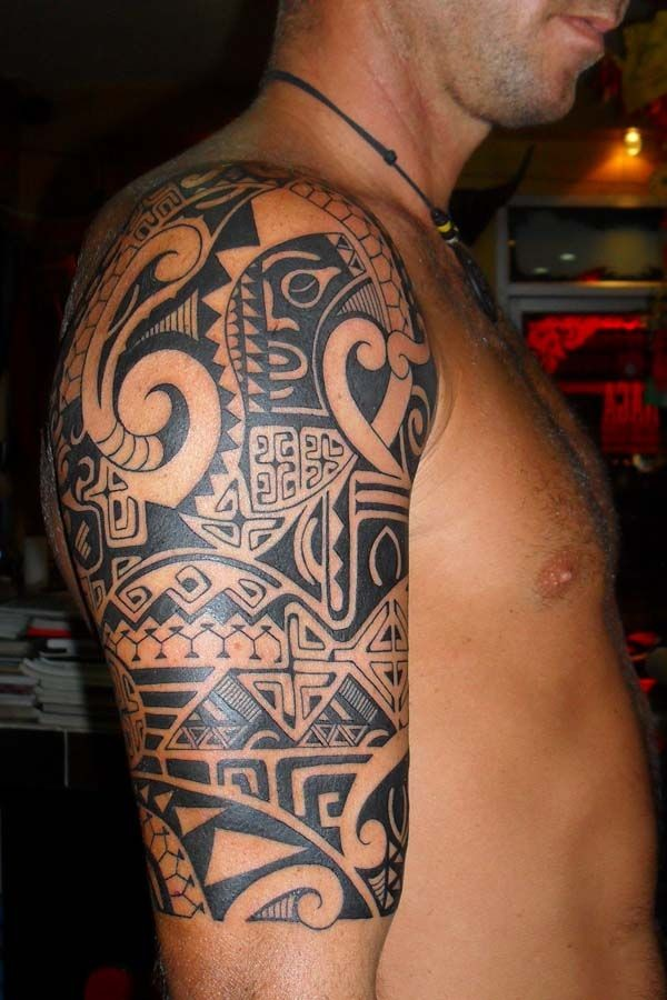 Polynesian style black ink shoulder tattoo of various ornaments