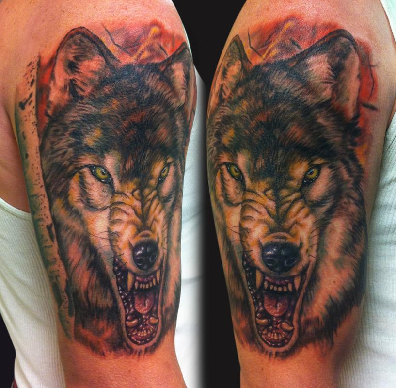 Tatuaggio carino sul deltoide il lupo con la bocca spalancata