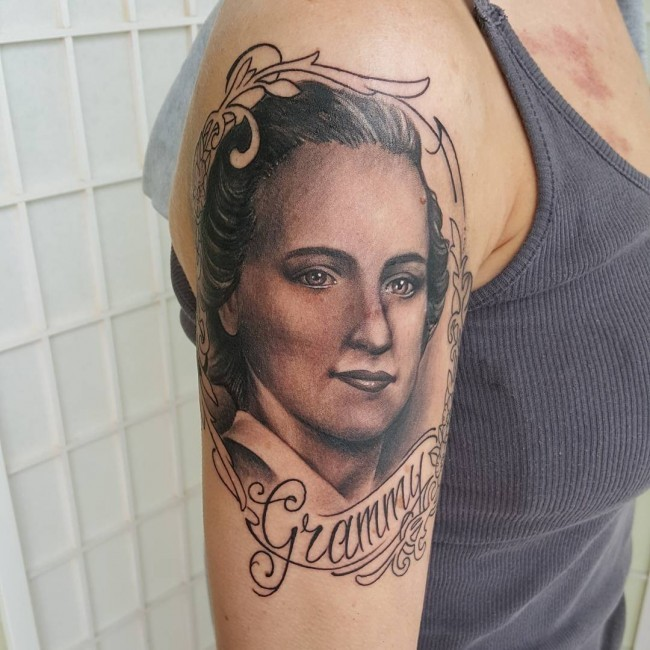 Portrait style black and gray style shoulder tattoo of woman with lettering