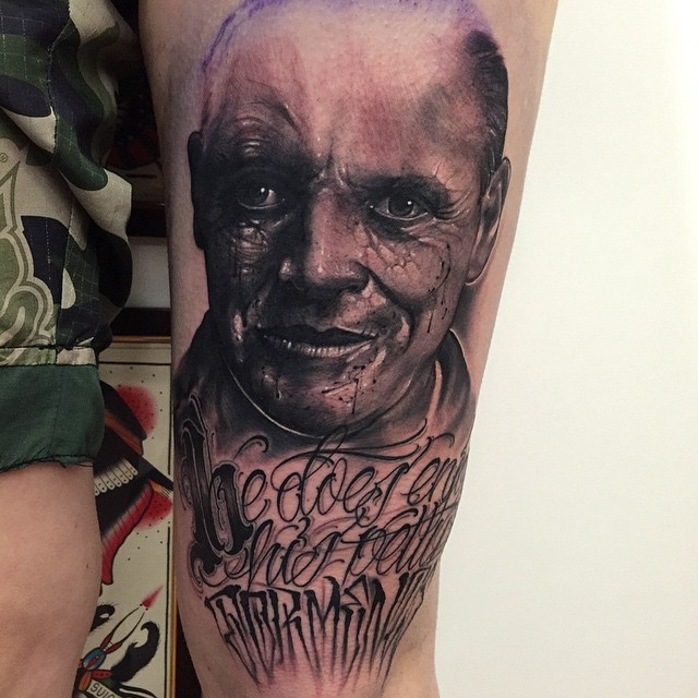 Portrait style black and white leg tattoo of creepy man portrait and lettering