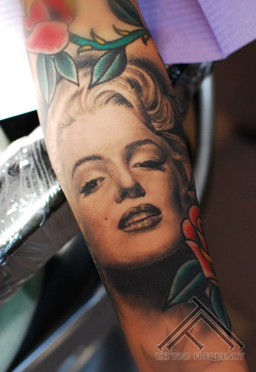 Portrait style black and white Marilyn Monroe face tattoo on forearm