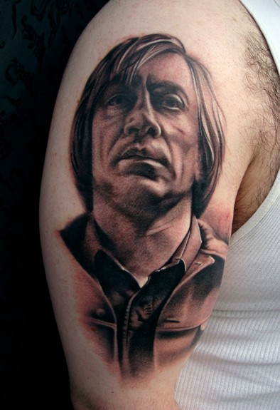 Portrait style black and white shoulder tattoo of man face