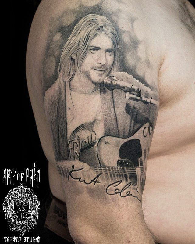 Portrait style black and white shoulder tattoo of Kurt Cobain with guitar
