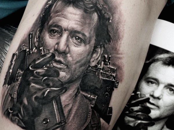 Portrait style black ink leg tattoo of famous actor face