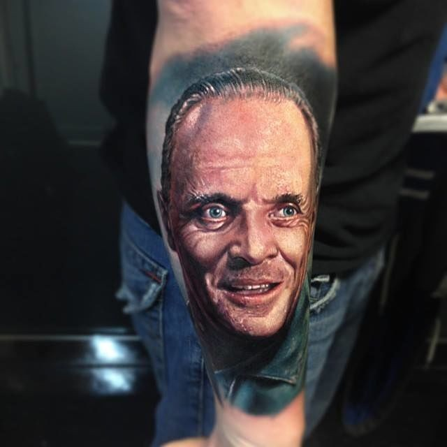 Portrait style colored arm tattoo of Hannibal Lector face