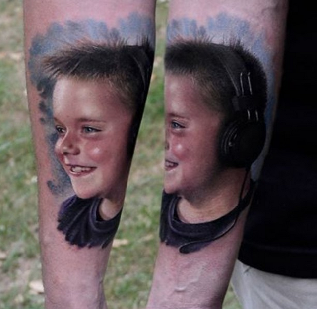 Portrait style colored arm tattoo of very detailed smiling boy