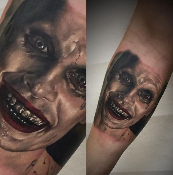 Portrait style colored forearm tattoo of creepy monster face