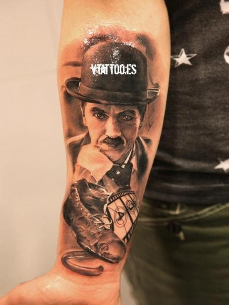 Portrait style colored forearm tattoo of Charlie Chaplin with old shoe
