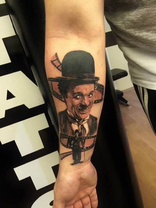 Portrait style colored forearm tattoo of cute Charlie Chaplin