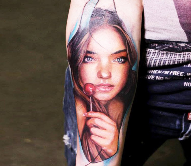 Portrait style colored forearm tattoo of girl with lollypop