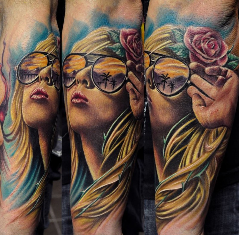 Portrait style colored forearm tattoo of woman with glasses and flower