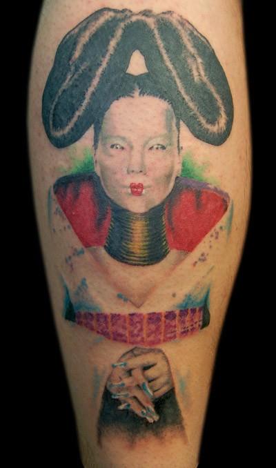 Portrait style colored leg tattoo of interesting looking geisha