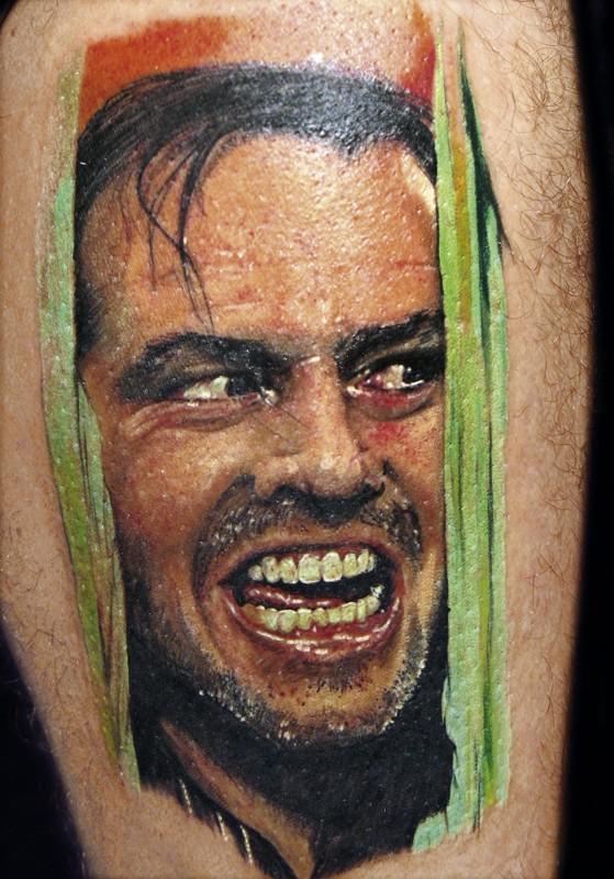 Portrait style colored leg tattoo of creepy movie scene