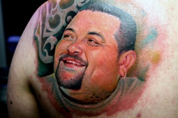 Portrait style colored scapular tattoo of mans face