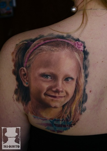 Portrait style colored scapular tattoo of cute girl face