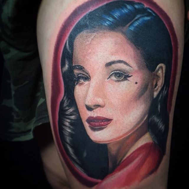 Portrait style colored shoulder tattoo of Dita Von Teese face