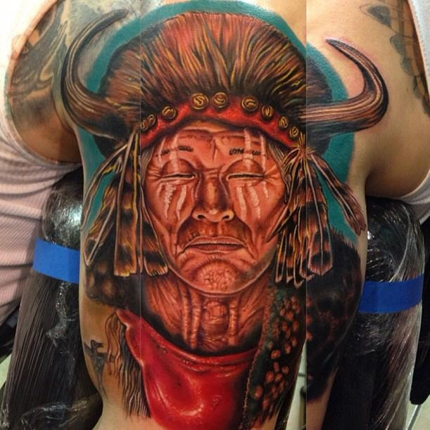 Portrait style colored shoulder tattoo of gorgeous Indian face with helmet