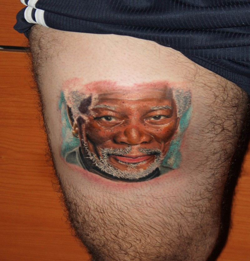 Portrait style colored thigh tattoo of famous actor face