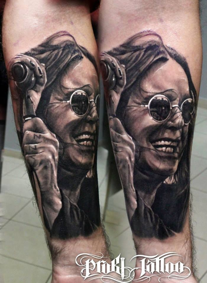 Portrait style detailed arm tattoo of famous musician with microphone