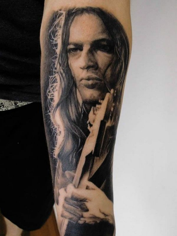 Portrait style detailed forearm tattoo of man with guitar