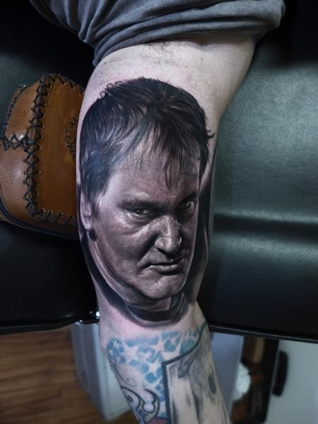Portrait style very detailed and colored biceps tattoo of angry man face