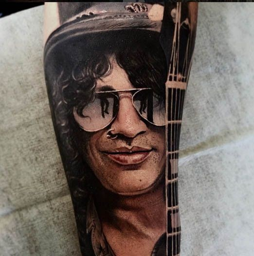 Portrait style very detailed arm tattoo of Slash face with guitar