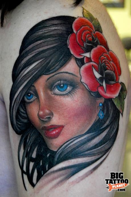 Pretty young brunette portrait with red roses in hair shoulder tattoo