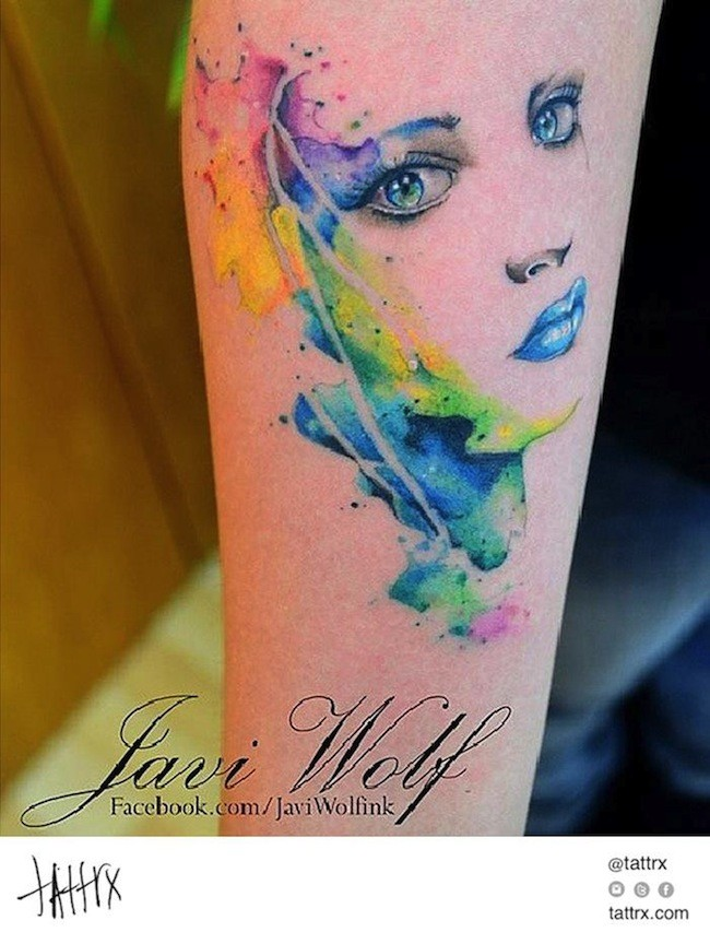 Pretty young girl&quots portrait with bright make up watercolor tattoo on arm by Javi Wolf
