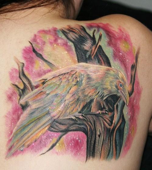 Tatuaggio colorato sulla spalla il corvo sul ramo
