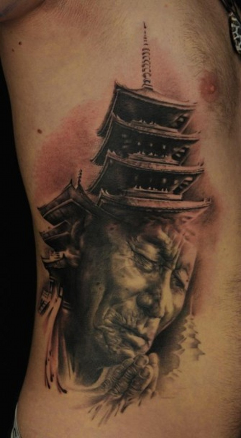 Real life style detailed praying old Asian monk tattoo on side combined with big temple