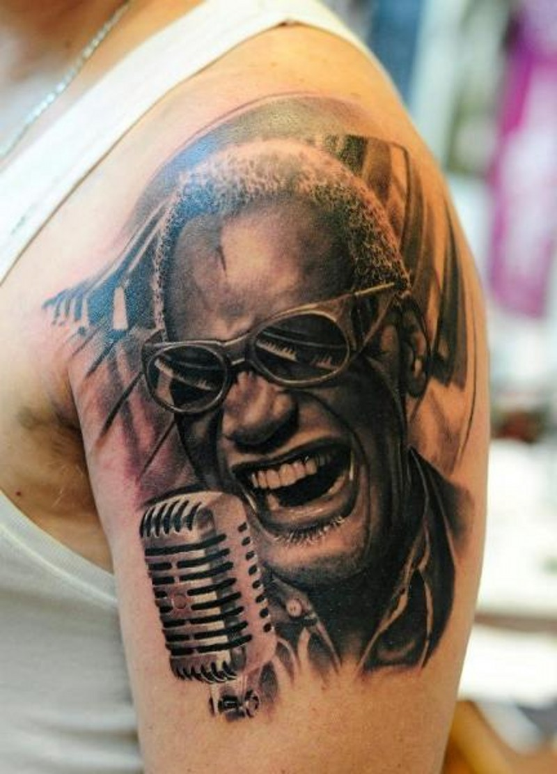 Real photo detailed black ink famous American singer tattoo on shoulder with piano keys