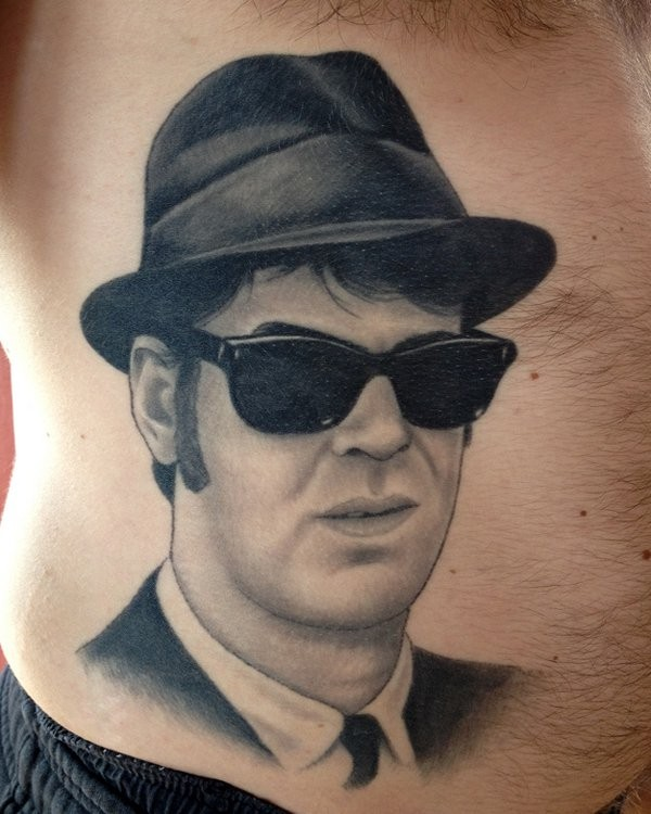Real photo like big black and white mystical man in sun glasses portrait tattoo on belly