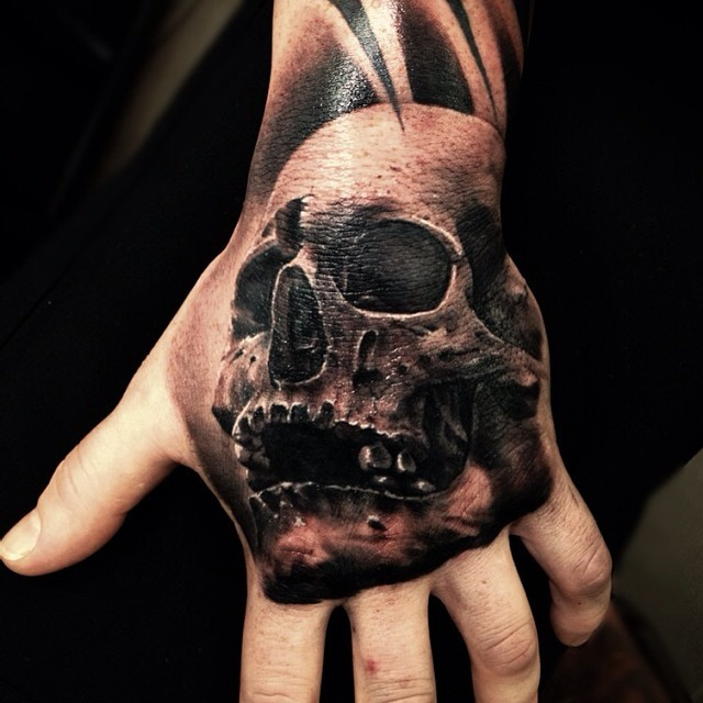 Real photo like colored 3D skull tattoo on hand