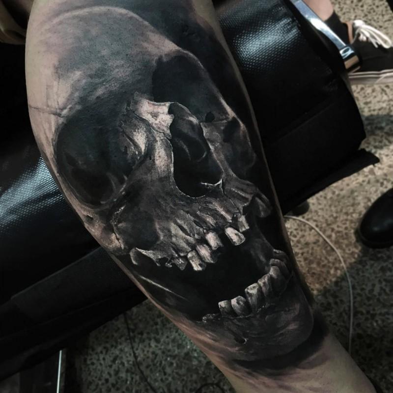 real photo like colored leg tattoo of creepy human skull by Eliot Kohek