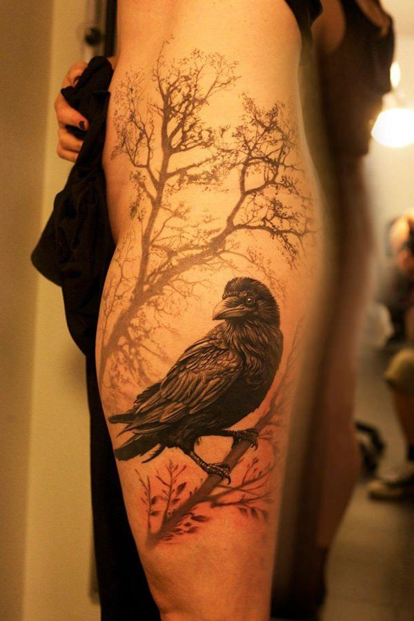 Real photo like colored very detailed crow tattoo on thigh stylized with lonely tree