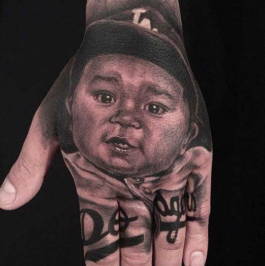 Real photo like natural looking black ink little baby portrait tattoo on hand with lettering