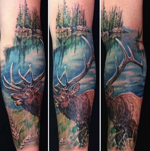 Realism style big natural colored forearm tattoo of deer on wild life and lake