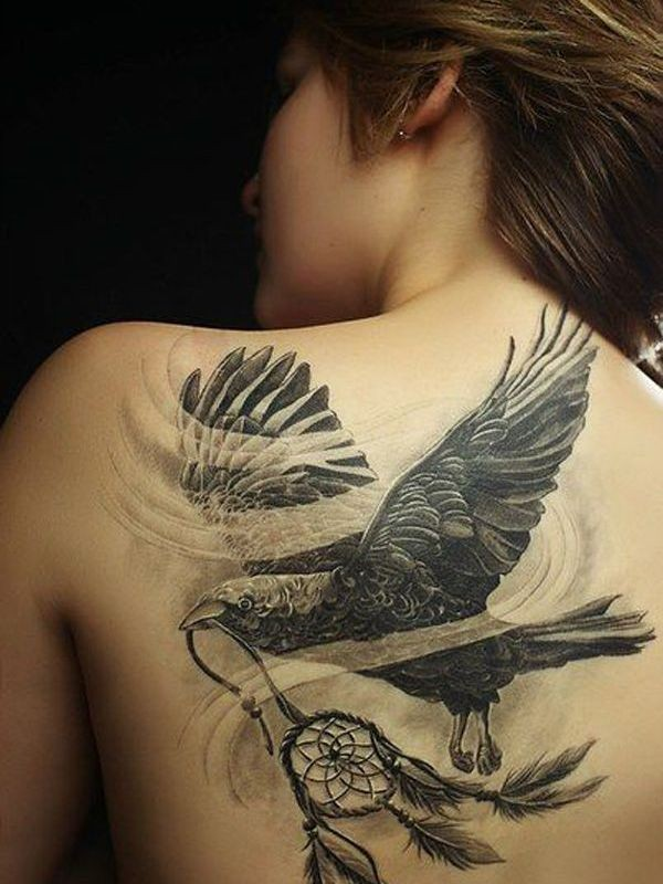 Realism style black and white back tattoo of crow with dream catcher