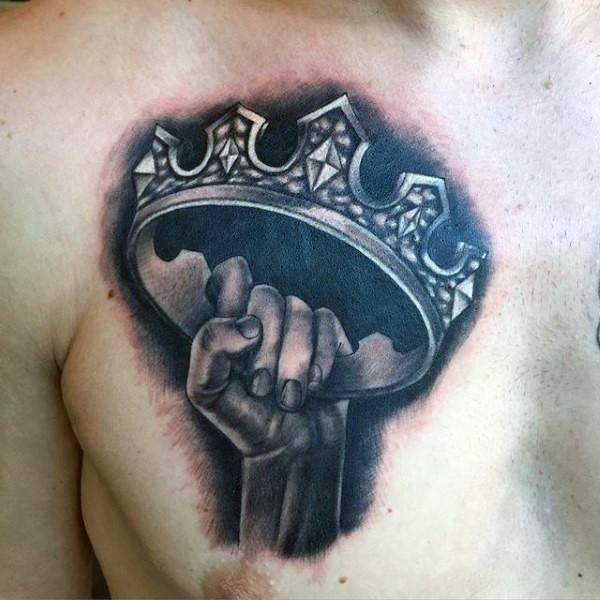 Realism style black and white chest tattoo of hand holding crown