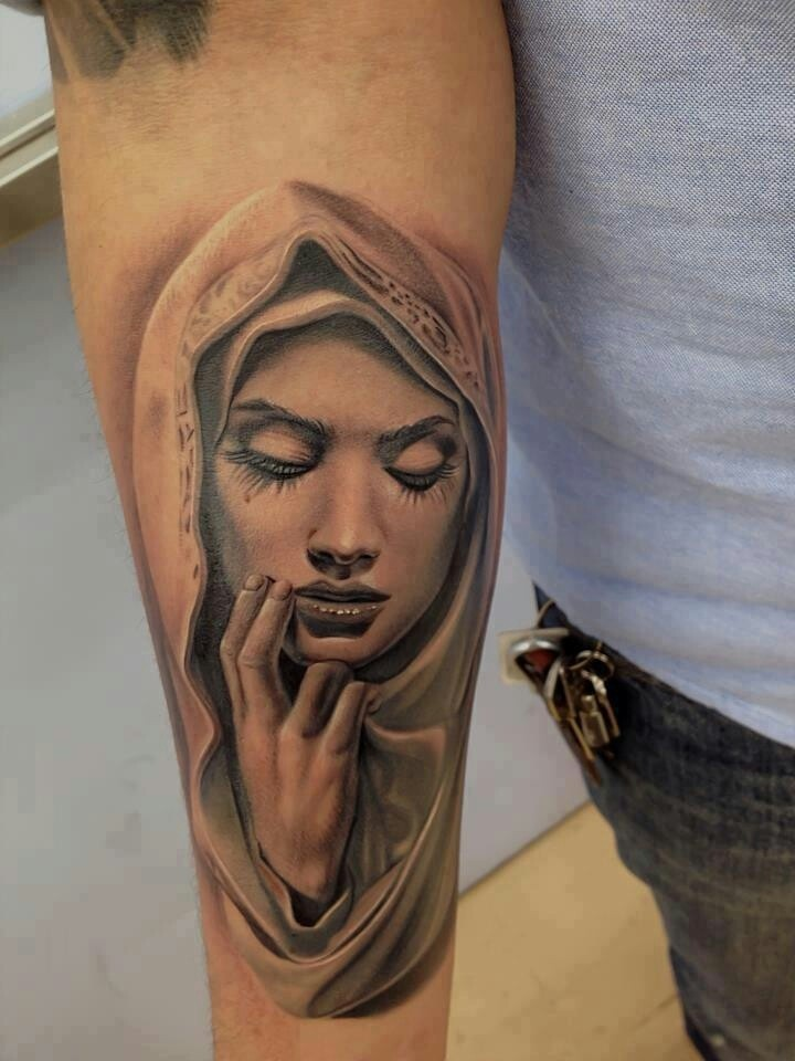 Realism style black and white forearm tattoo of woman in hood