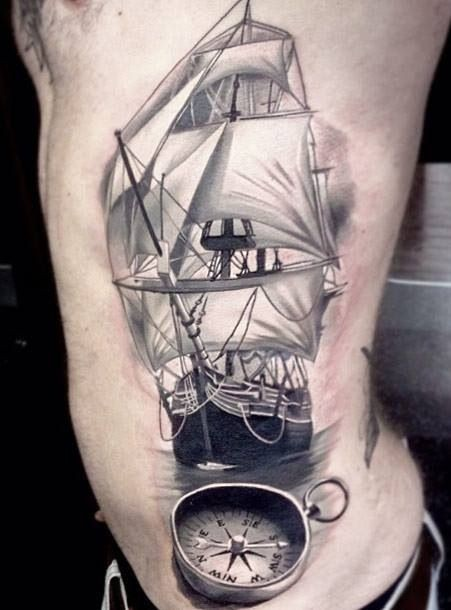 Realism style black and white large side tattoo of sailing ship with compass