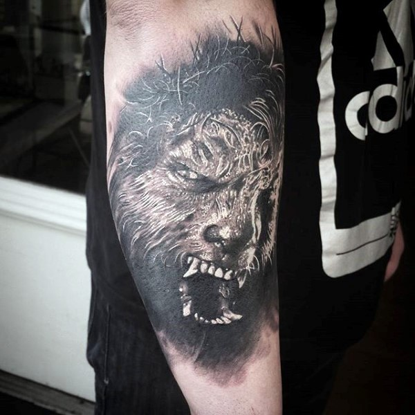 Realism style black and white werewolf face tattoo on forearm