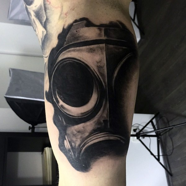 Realism style black ink biceps tattoo of gas mask part