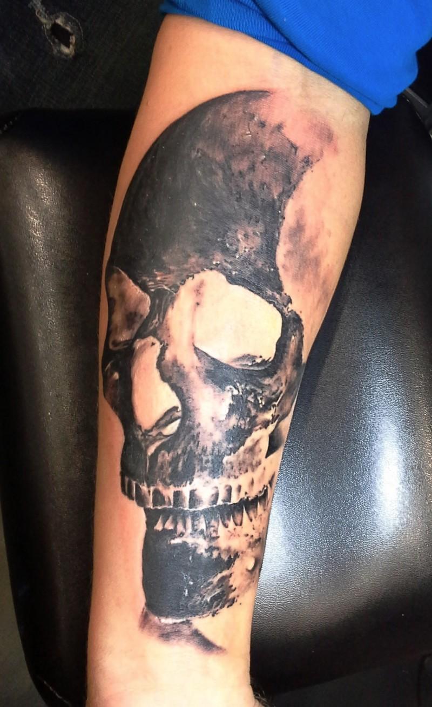 realism style black ink forearm tattoo of big human skull