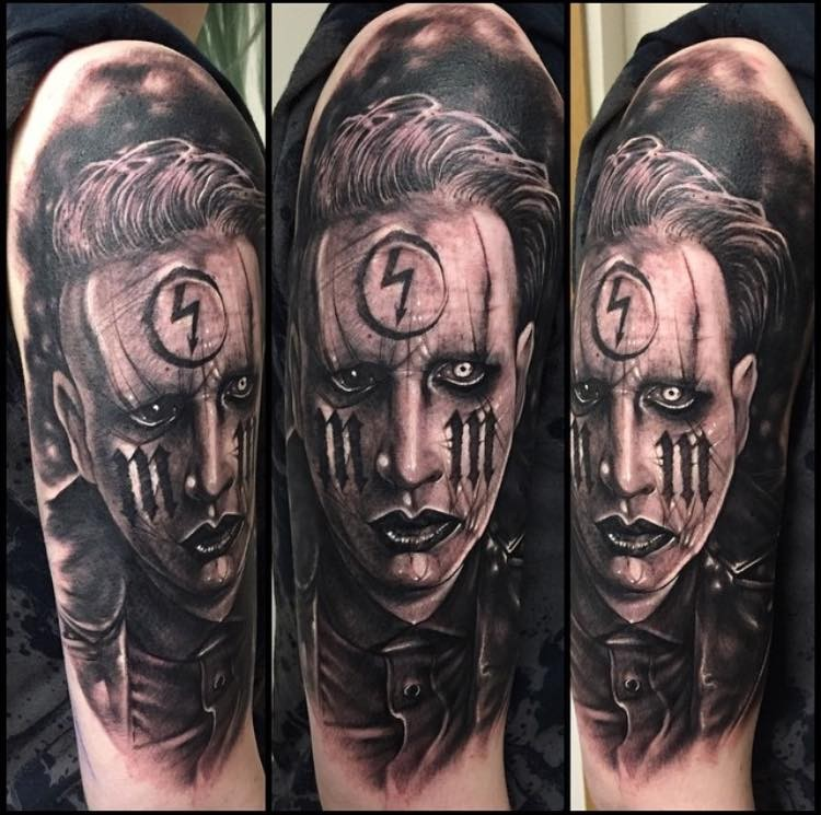 Realism style black ink Merlin Manson portrait tattoo on shoulder stylized with various symbols