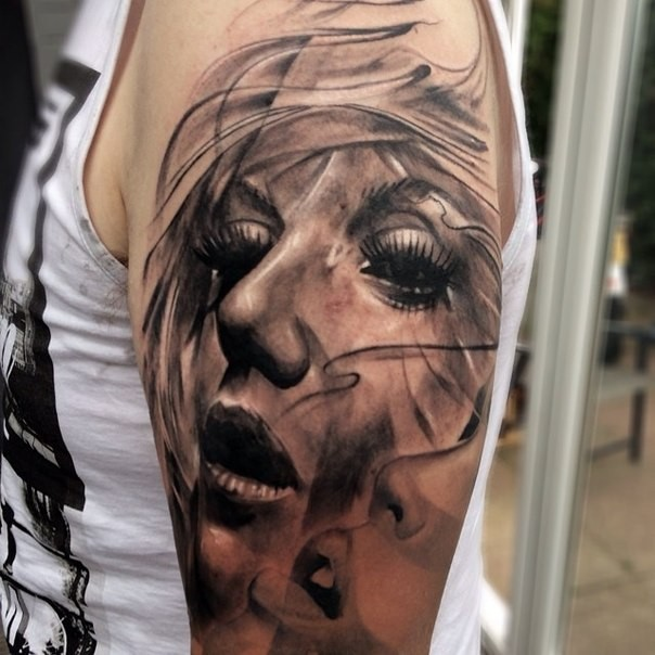 Realism style black ink shoulder tattoo of woman face