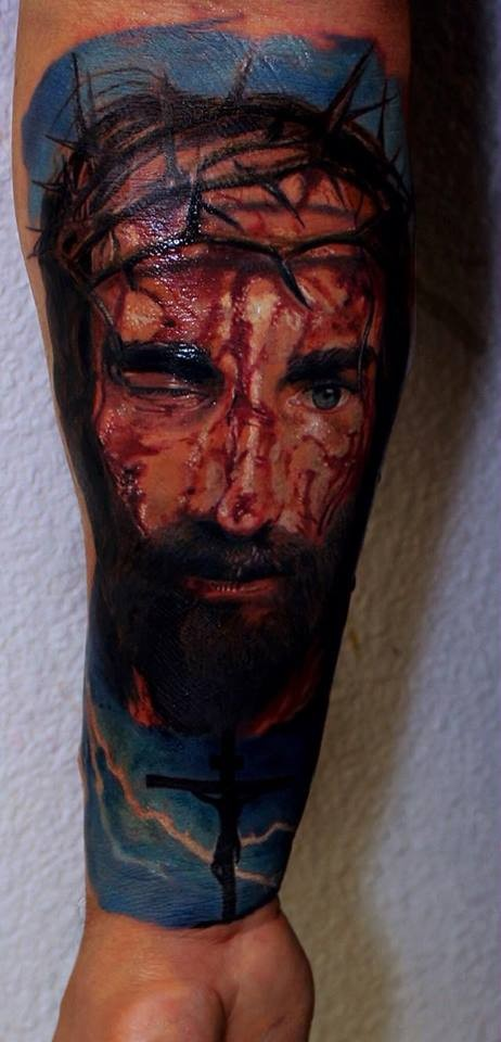 Realism style colored arm tattoo of bloody Jesus face with vine
