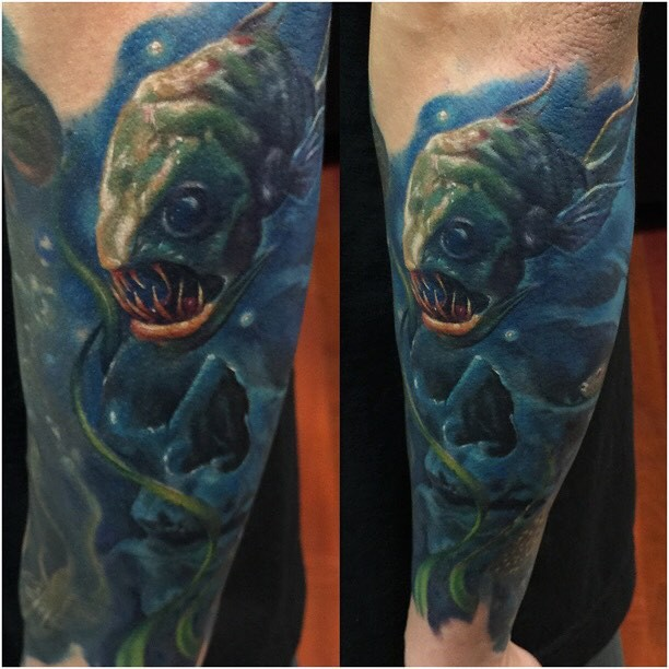 Realism style colored arm tattoo of creepy looking fish