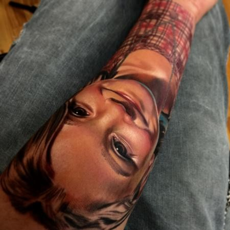 Realism style colored arm tattoo of smiling boy portrait